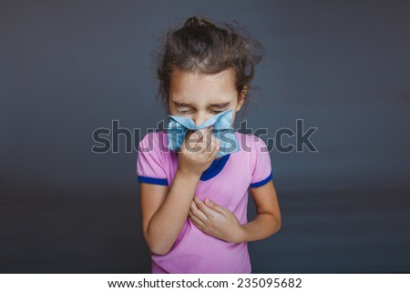 girl blowing his nose into a handkerchief on a gray background - stock photo