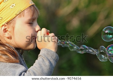 Girl blowing soap bubbles oudoors