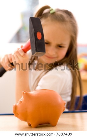 Girl breaking the piggy bank with hammer [focus on pig] - stock photo