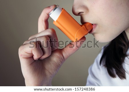 Girl breathing asthmatic medicine health-care inhaler - stock photo