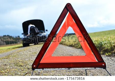 Girl, broken car and triangle - stock photo