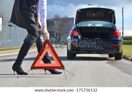Girl, broken car and warning triangle - stock photo