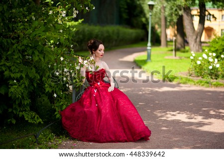 Girl brunette in a red dress in a lush park