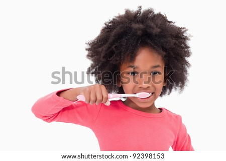 Girl brushing her teeth against a white background - stock photo