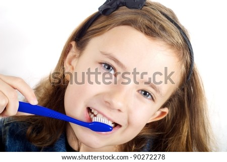 Girl brushing teeth on white background - stock photo