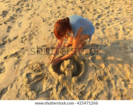 Girl building a castle on the beach, woman & yellow beach castle, sand castle and girl, building a castle on beach, beach sculpture castle, girl making a sand castle, girl on beach with sand sculpture - stock photo