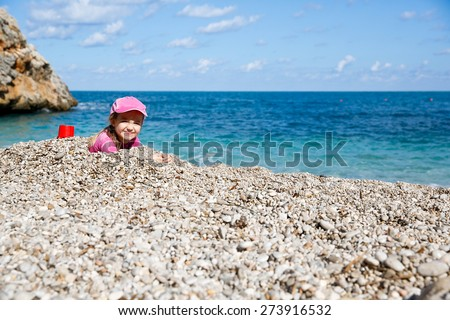 Girl buried in beach pebbles, smiling and enjoying free time on the beach, dressed in wetsuit and a hat for sun protection. Family and children on vacation, summer fun concept.  - stock photo