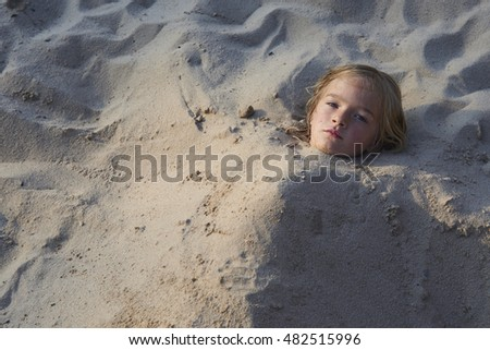 Girl Buried in the Sand at the Beach