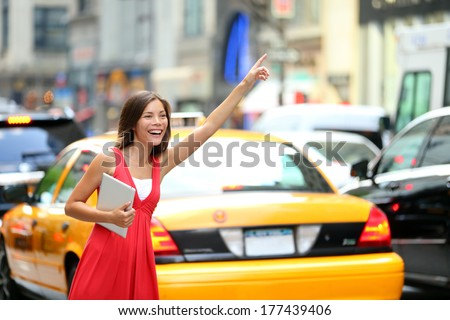 Girl calling taxi cab in New York City, holding tablet pc computer standing in cute summer dress in street of Manhattan, USA. Beautiful young mixed race Asian Caucasian woman outdoor. - stock photo