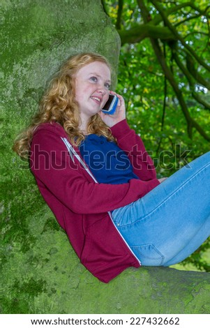 Girl calling with mobile phone in green tree - stock photo