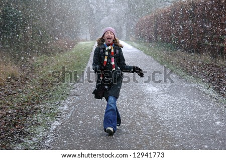 girl catching snowflakes on tongue - stock photo