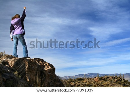 Girl celebrating victory after climbing a rock.