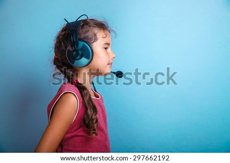 Girl child in headphones with a microphone sideways in profile on a blue background photo studio - stock photo