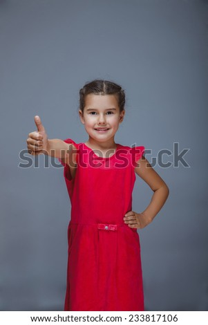 girl child in red dress showing thumbs up sign yes on a gray background