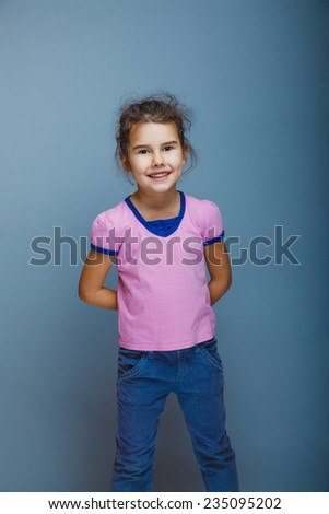 girl child standing clasped her hands behind her back on a gray background - stock photo