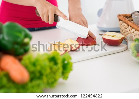 Girl chopping apple to prepare healthy low-calorie diet - stock photo