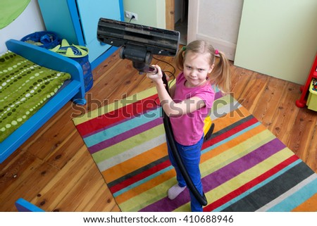 girl cleaning floor with hoover , The girl is vacuuming the carpet   - stock photo