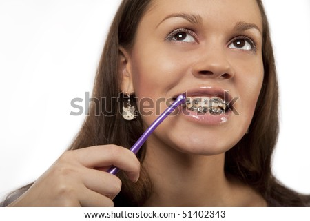 girl cleaning teeth with bracket system using roung toothbrush isolated over white - stock photo