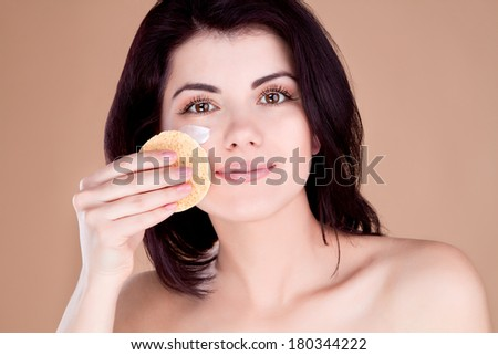 Girl cleans the skin from the face cream sponge - stock photo