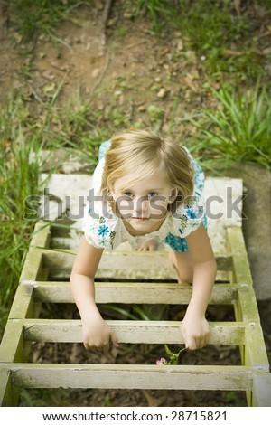 Girl climbing ladder into tree house - stock photo