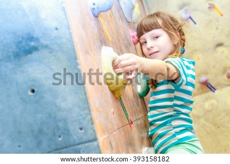 Girl climbing on practical wall indoor, bouldering training