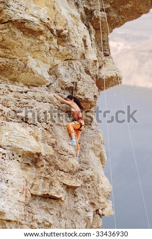 girl climbing on the rock on background - stock photo