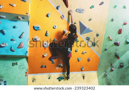 Girl climbing up on practice wall in gym, rear view - stock photo