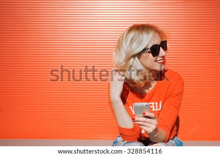 girl close-up of a beautiful young blonde in the street lifestyle  hipster on a red background with red lips smiling in sunglasses with her hands with a red manicure with a telephone selfie hipster - stock photo