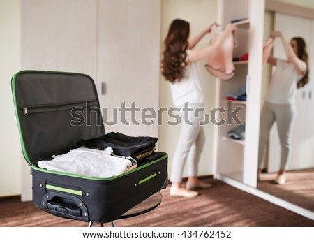 Girl collects a suitcase in a hotel room. - stock photo