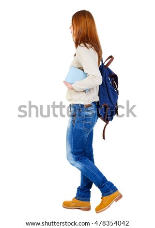 Girl comes with stack of books. side view. girl with the blue backpack in a white blouse goes right with a stack of books.