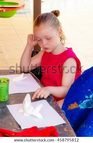 Girl considering the figures for painting