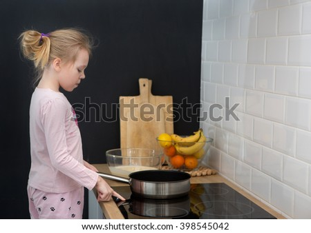 girl cooking pancakes in kitchen