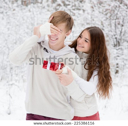 girl covering boyfriends eyes with hands and giving a gift - stock photo