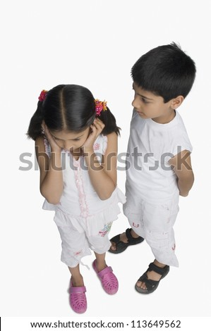 Girl covering her ears while her brother talking - stock photo