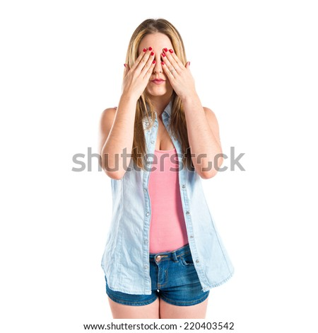 Girl covering her eyes over isolated white background