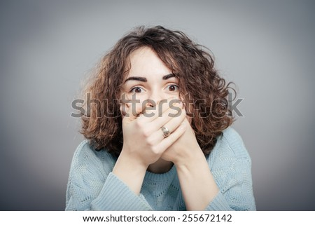 girl covering her mouth with her hands, scared on a gray background - stock photo