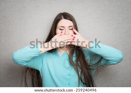 girl covers her mouth with her hands - stock photo