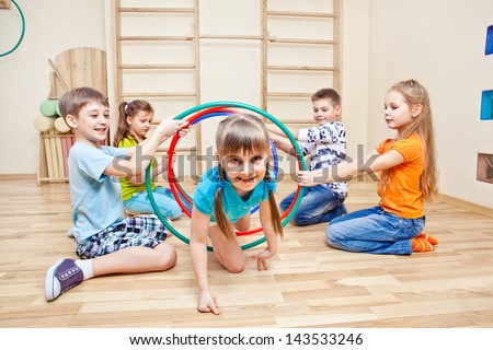 Girl crawling through hula hoops - stock photo