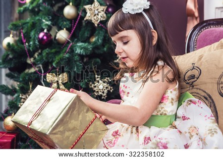 Girl curiously opening a golden present box. Christmas gifts and surprises. Merry Christmas and happy New Year! A series of photos