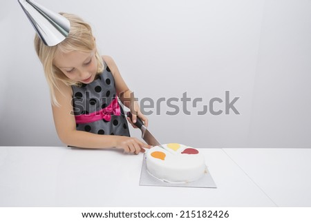 Girl cutting birthday cake at table in house - stock photo