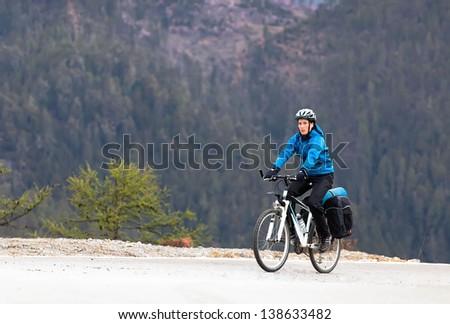 Girl cyclist among the high mountains of the Himalayas - stock photo