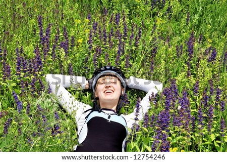 Girl cyclist in sportive clothes and helmet taking rest in green grass and flowers - stock photo