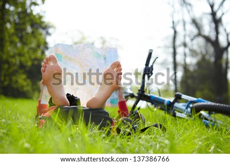 Girl cyclist reads a map lying barefoot on green grass outdoors in summer park. Enjoying relaxation