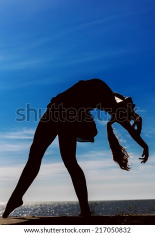 Girl dances on the beach at sunset. Natural light and darkness. Artistic colors added.  - stock photo