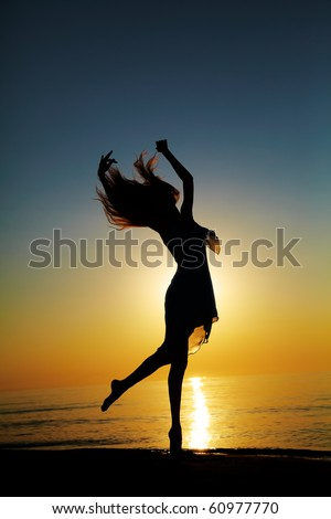 Girl dances on the beach at sunset. Natural light and darknesss. Artistic colors added. Vertical photo - stock photo