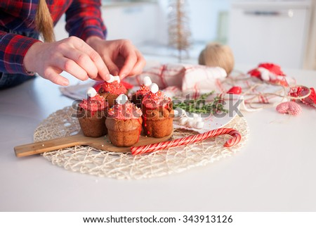 Girl decorates New Year celebration cupcakes, chocolate muffins on table - stock photo
