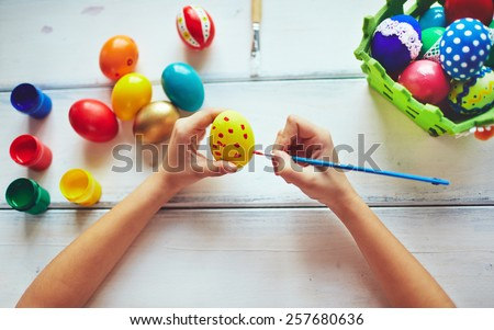 Girl decorating Easter eggs - stock photo
