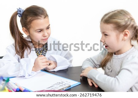 Girl doctor listening to a young patient, kids playing - stock photo