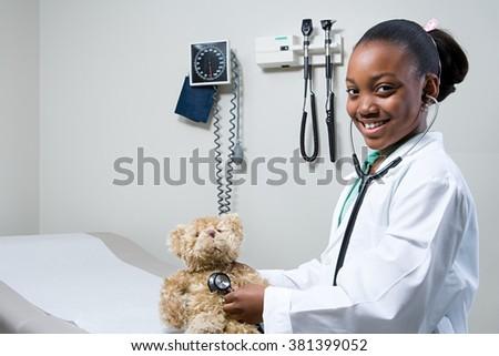 Girl doctor using stethoscope on teddy bear - stock photo