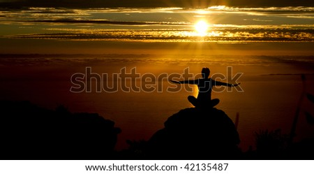 Girl does yoga at sunset on top of a mountain - stock photo